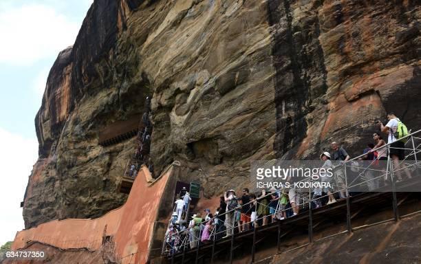 Sri Lankans and tourists climb the 80metre fortress of Sigiriya rock in Sigiriya northcentral Sri Lanka on February 11 2017 The Sigiriya rock 160...