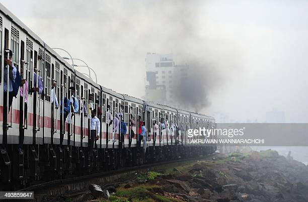 Sri Lankans hold on to the sides of passenger train in Colombo on May 26 2014 Train travel is a popular mode of transport in this nation of 20...