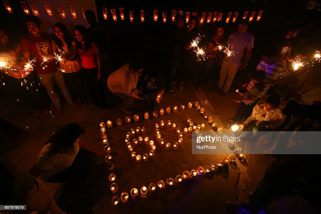 Sri Lankans light lamps to form the number 60, representing the 60 minutes of Earth Hour, during Earth Hour in Colombo, Sri Lanka March 25, 2017.