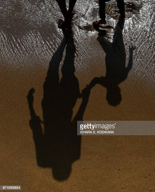 Sri Lankans stand at the water's edge at Galle Face Beach in the heart of the Sri Lankan capital Colombo on November 15 2017 / AFP PHOTO / ISHARA S...
