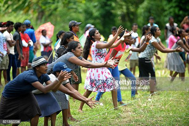 Sri Lankan's take part in a traditional 'Catch the Egg Toss' game in a field during Sinhala and Tamil New Year celebrations in Kirindiwela on April...