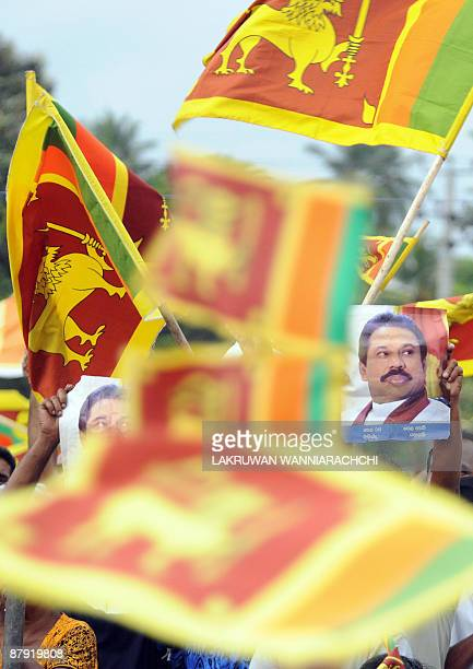 Sri Lankans wave national flags as unseen President Mahinda Rajapakse arrives at a festival to celebrate the defeat of Tamil Tiger rebels in Colombo...