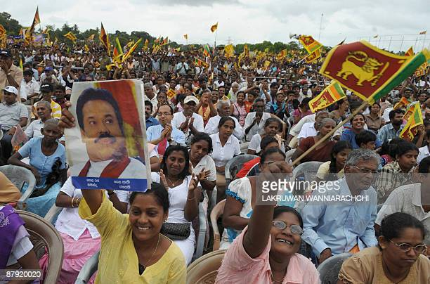Sri Lankans wave national flags as unseen President Mahinda Rajapakse arrives at a festival to celebrate the defeat of the Tamil Tiger rebels in...