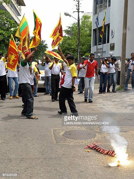 Sri Lankans wave the national flag and light fire crackers as they celebrate the return of Sri Lankan President Mahinda Rajapakse from Jordan to a...