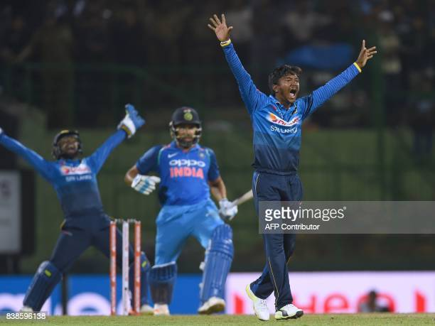 Sri Lanka's Akila Dananjaya celebrates after he dismissed Indian batsman Rohit Sharma as Sri Lankan wicketkeeper Niroshan Dickwella reacts during the...