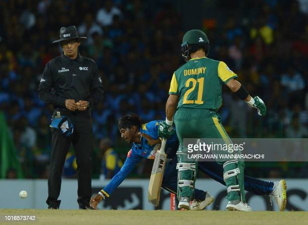 Sri Lanka's Akila Dananjaya dives as he attempts to field a ball as South Africa's JP Duminy look on during the international Twenty20 cricket match...