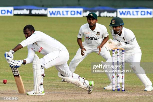Sri Lanka's Angelo Mathews plays a shot as Bangladesh's wicketkeeper Liton Das and teammate Mehidy Hasan Miraz watch during the third day of the...