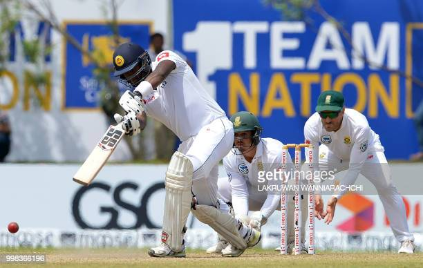 Sri Lanka's Angelo Mathews plays a shot in front of South Africa's wicketkeeper Quinton de Kock and Faf du PLessis during the third day of the...