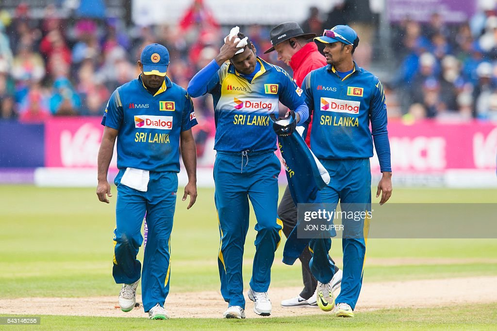 Sri Lanka's Angelo Mathews, (C) wipes his face as he walks from the pitch with teammates as rain stops play in the third one day international (ODI) cricket match between England and Sri Lanka at Bristol cricket ground in Bristol, south-west England, on June 26, 2016. Chris Woakes and Liam Plunkett both took three wickets apiece as England held Sri Lanka to 248 for nine in the third one-day international at Bristol on Sunday. / AFP / JON