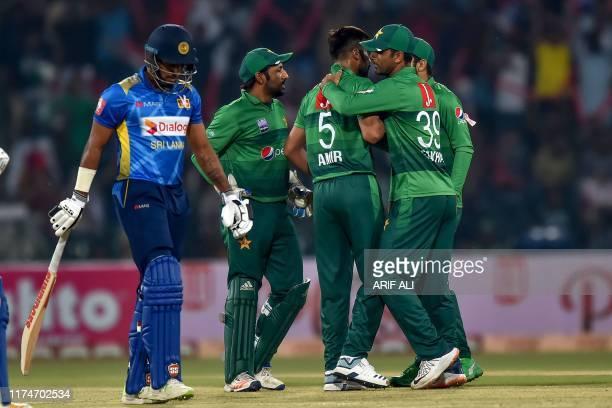 Sri Lanka's batsman Danushka Gunathilaka walks back to the pavilion after his dismissal as Pakistan's cricketers celebrate during the third and final...