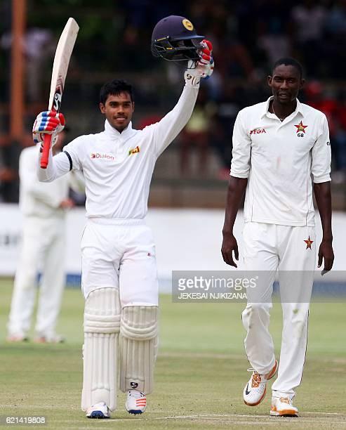 Sri Lanka's batsman Dhananjaya de silva raises his bat to celebrate a 100 runs as Zimbabwe's Christopher Mpofu looks on during the first day of the...