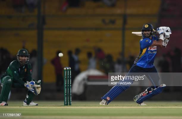 Sri Lanka's batsmen Dasun Shanaka plays a shot as Pakistan's captain and wicketkeeper Sarfraz Ahmed looks on during the second one day international...