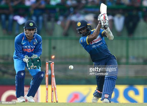 Sri Lanka's captain Chamara Kapugedera is bowled out by India's Jasprit Bumrah is watched by Indian wicketkeeper Mahendra Singh Dhoni during the...