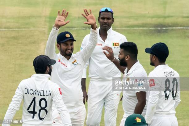 Sri Lanka's captain Dimuth Karunaratne celebrates with teammates after the dismissal of Zimbabwe's Kevin Kasuza during the first day of the first...
