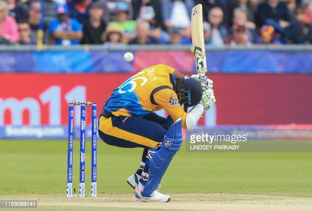 TOPSHOT Sri Lanka's captain Dimuth Karunaratne ducks to avoid a bouncer during the 2019 Cricket World Cup group stage match between Sri Lanka and...