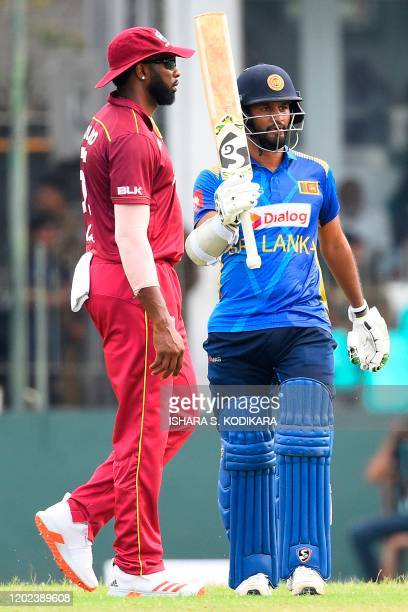 Sri Lanka's captain Dimuth Karunaratne reacts after scoring a halfcentury as West Indies' captain Kieron Pollard looks on during the first one day...