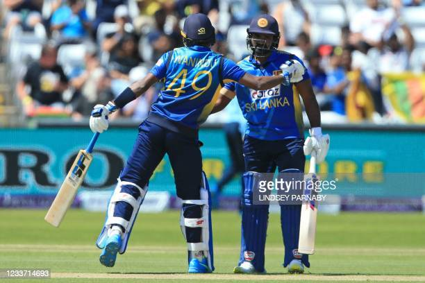 Sri Lanka's captain Kusal Perera is congratulated by Sri Lanka's Wanindu Hasaranga after reaching 50 runs during the first one-day international...
