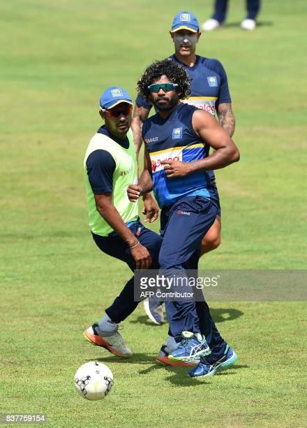 Sri Lanka's coach Nic Pothas plays football with players Lasith Malinga and Danushka Gunathilaka during a practice session at the Pallekele...