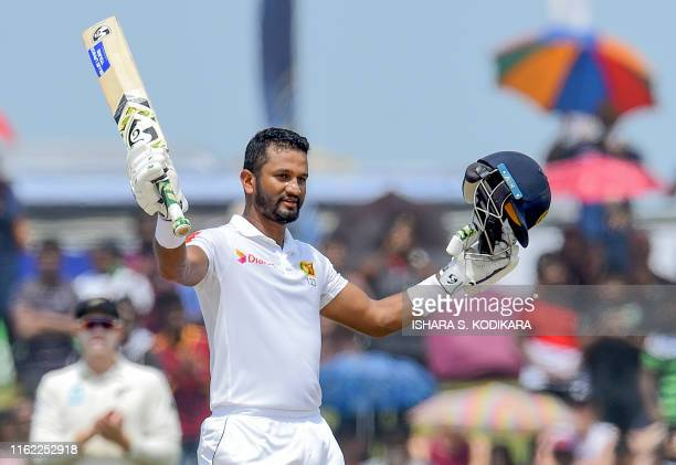 Sri Lanka's cricket team captain Dimuth Karunaratne celebrates after scoring a century during the final day of the opening Test cricket match between...