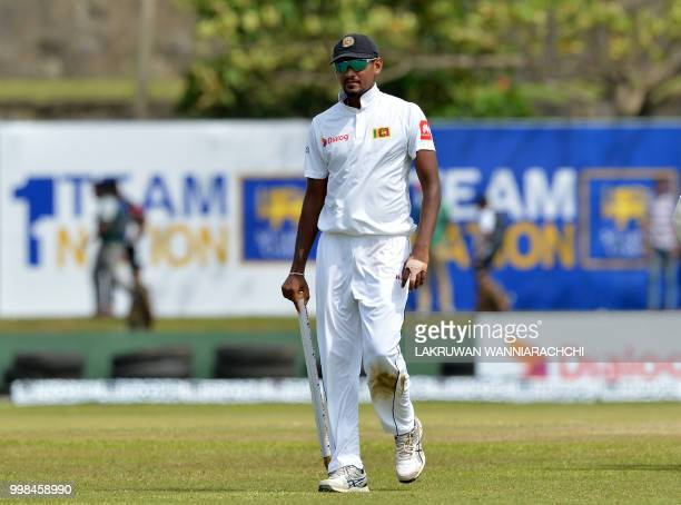 Sri Lanka's cricket team captain Suranga Lakmal leaves the grounds with the stumps after victory in the opening Test match between Sri Lanka and...