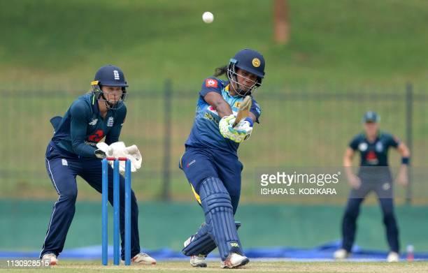 Sri Lanka's cricketer captain Chamari Atapattu plays a shot as England's Amy Jones looks on during the first one day international cricket match...