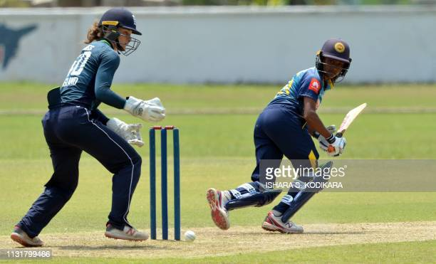 Sri Lanka's cricketer Harshitha Madavi plays a shot as England's wicketkeeper Amy Jones looks on during the third one day international cricket match...
