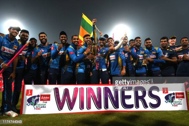 Sri Lanka's cricketers pose for a photograph with winning trophy during the third and final Twenty20 International cricket match between Pakistan and...