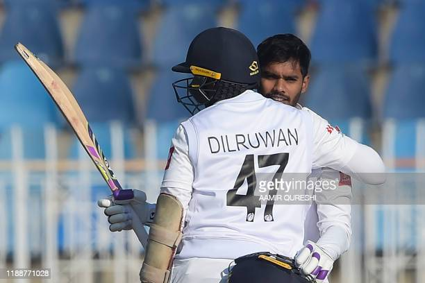 Sri Lanka's Dhananjaya de Silva celebrates with teammate Dilruwan Perera after scoring a century during the fifth and final day of the first Test...