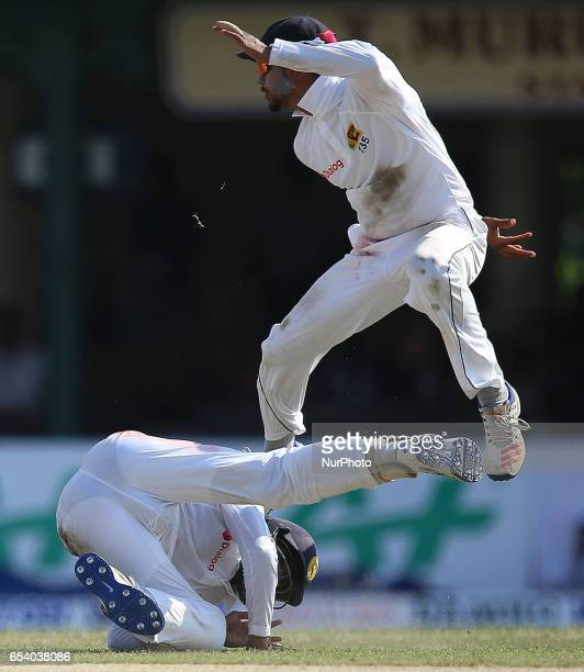 Sri Lanka's Dhananjaya De Silva leaps in the air to avoid colliding with Kusal Mendis during the second day of the second and final Test cricket...