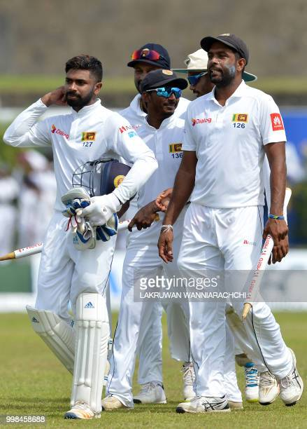 Sri Lanka's Dilruwan Perera and teammates leave the grounds with the stumps after victory in the opening Test match between Sri Lanka and South...
