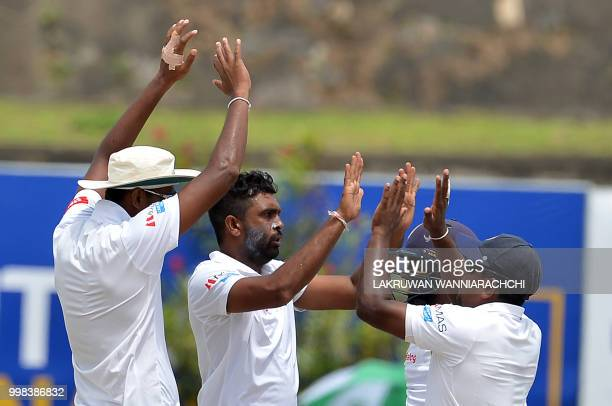 Sri Lanka's Dilruwan Perera celebrates with his teammates after he dismissed South Africa's Hashim Amla during the third day of the opening Test...