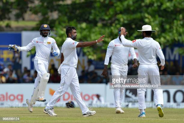 Sri Lanka's Dilruwan Perera celebrates with his teammates after he dismissed South Africa's Keshav Maharaj during the third day of the opening Test...