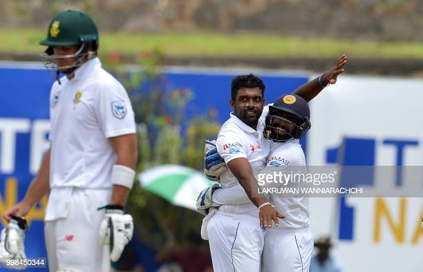 Sri Lanka's Dilruwan Perera celebrates with wicketkeeper Niroshan Dickwella after he dismissed South Africa's Hashim Amla during the third day of the...