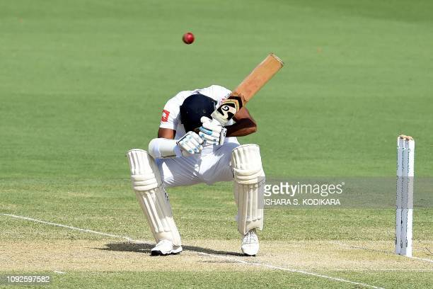 TOPSHOT Sri Lanka's Dimuth Karunaratne avoids a bouncer ball by Australia's Pat Cummins during day two of the second Test cricket match between...