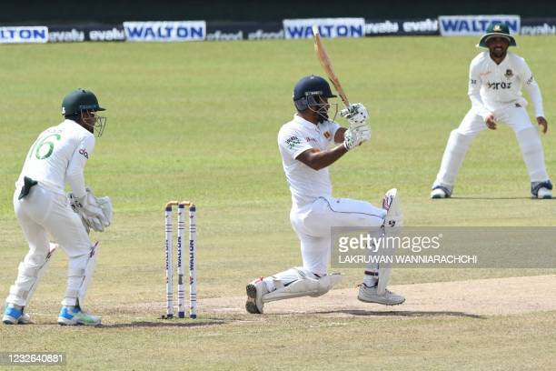 Sri Lanka's Dimuth Karunaratne plays a shot as Bangladesh's wicketkeeper Liton Das watches during the fourth day of the second and final Test cricket...