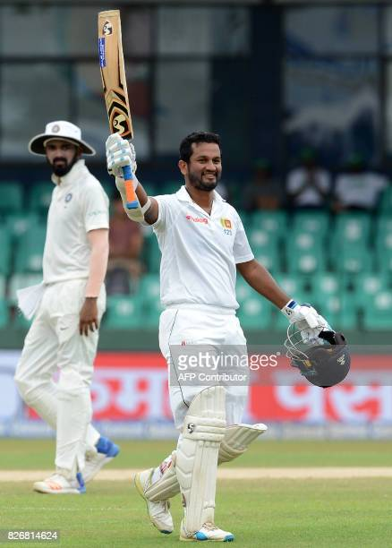 Sri Lanka's Dimuth Karunaratne raises his bat and helmet in celebration after scoring a century during the fourth day of the second Test match...