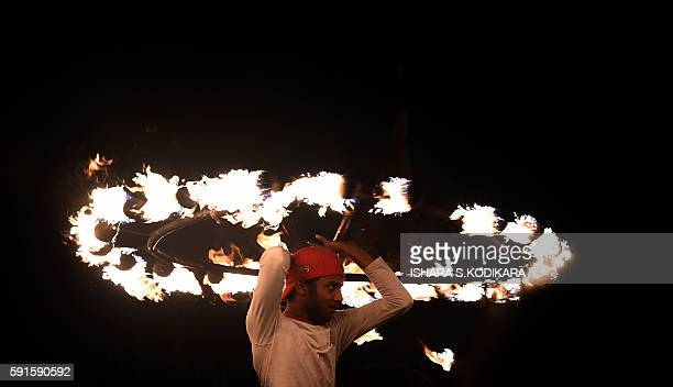 Sri Lanka's fire-dancer performs in front of the historic Buddhist Temple of the Tooth, as he takes part in a procession during the Esala Perahera...