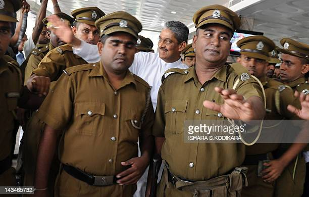 Sri Lanka's former army chief Sarath Fonseka is escorted from jail to a Colombo hospital by security officers on April 27, 2012. Fonseka was taken to...