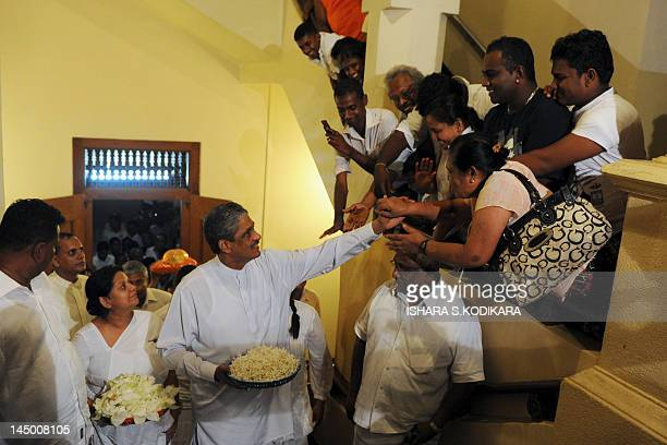 Sri Lanka's former army chief Sarath Fonseka with wife Anoma shakes hands with supporters at the Buddhist temple of Tooth in the central town of...