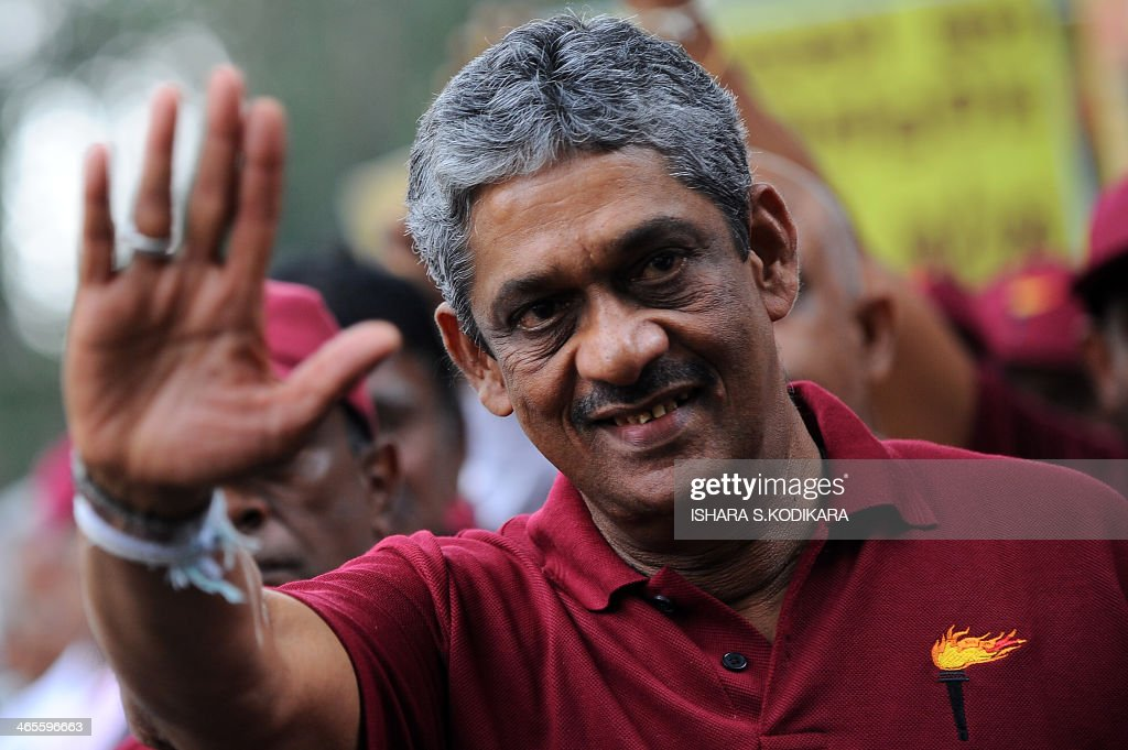 Sri Lanka's former army-chief-turned-opposition-politician Sarath Fonseka waves to supporters at a public rally in the capital Colombo on January 28, 2014. Fonseka's Democratic Party is protesting against high living costs and corruption, but is not joining other opposition parties which were holding separate anti-government rallies. AFP PHOTO/Ishara S. KODIKARA