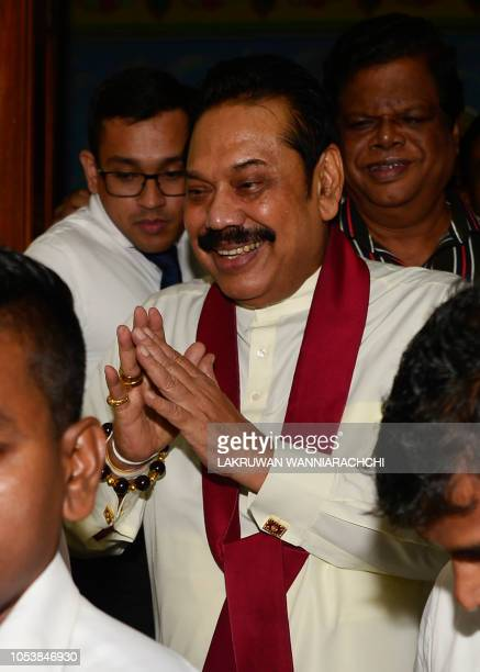 Sri Lanka's former president and new prime minister Mahinda Rajapaksa leaves a temple where he offered prayers after having been sworn in as prime...