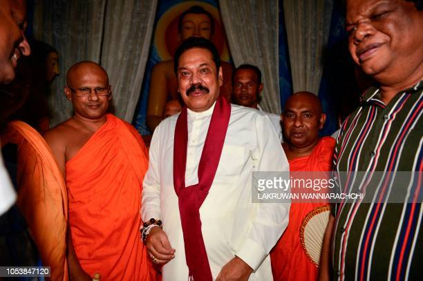 Sri Lanka's former president and new prime minister Mahinda Rajapaksa receives blessings from a Buddhist monk as he offers prayers at a temple after...