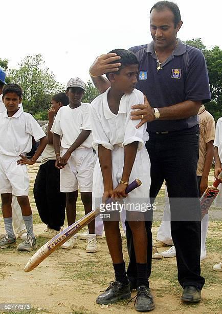 Sri Lanka's former test skipper Hashan Tilakaratne coaches a Tamil youngster 08 May 2005 in the rebelheld town of Kilinochchi in northern Sri Lanka...
