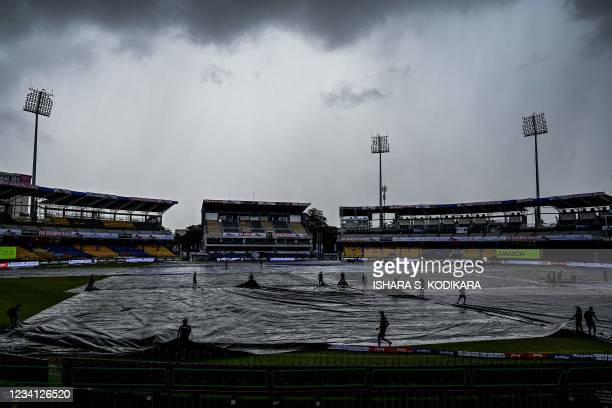Sri Lanka's ground staff personnel cover the ground as rain stops play during the third one-day international cricket match between Sri Lanka and...