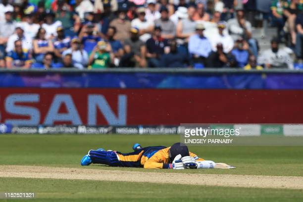 Sri Lanka's Isuru Udana lies on the field as bees swarm during the 2019 Cricket World Cup group stage match between Sri Lanka and South Africa at the...