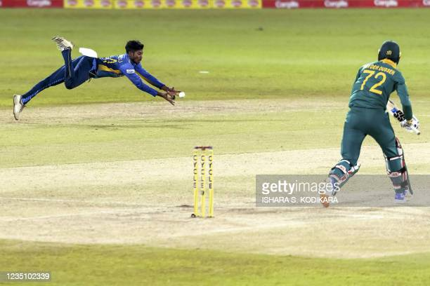 Sri Lanka's Kamindu Mendis dives to take a catch to dismiss South Africa's Rassie van der Dussen during the third one-day international cricket match...