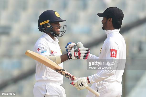 Sri Lanka's Kusal Mendis celebrates with teammate Dhananjaya de Silva after scoring a century during the third day of the first cricket Test between...