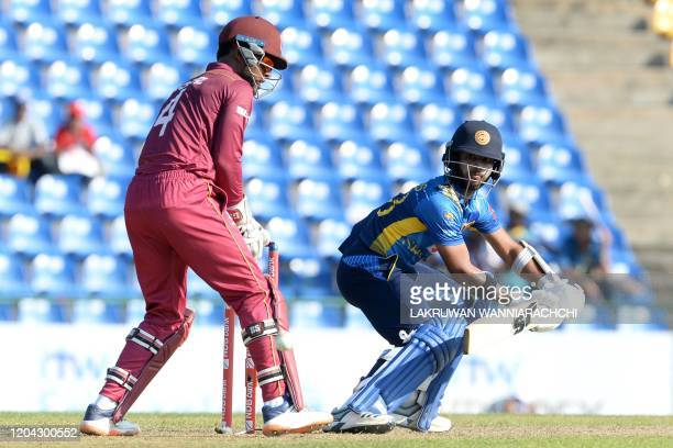 Sri Lanka's Kusal Mendis plays a shot as West Indies' Shai Hope looks on during the third one day international cricket match between Sri Lanka and...