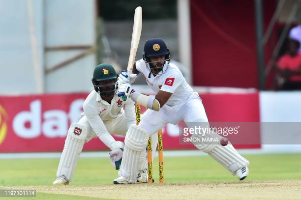 Sri Lanka's Kusal Mendis plays a shot as Zimbabwe's Regis Chakabva looks on during the second day of the second Test cricket match between Zimbabwe...