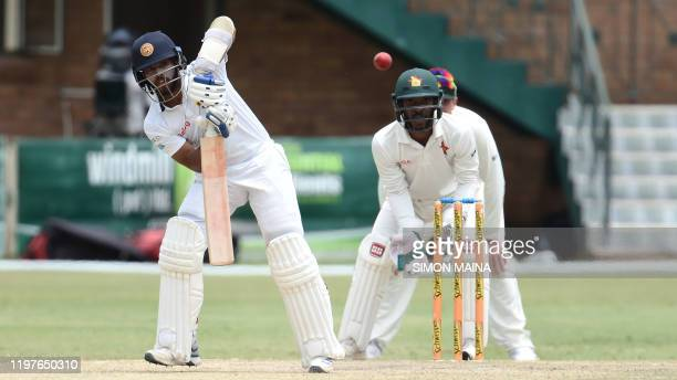 Sri Lanka's Kusal Mendis watches the ball after playing a shot as Zimbabwe's Regis Chakabva looks on during the fifth day of the second Test cricket...